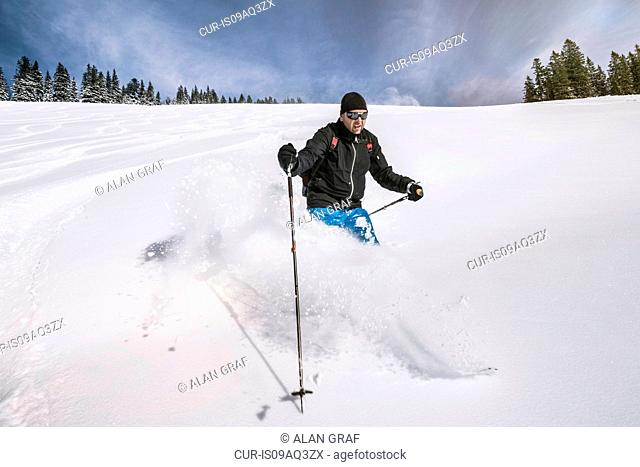 Man skiing down snow covered slope, Spitzingsee, Germany