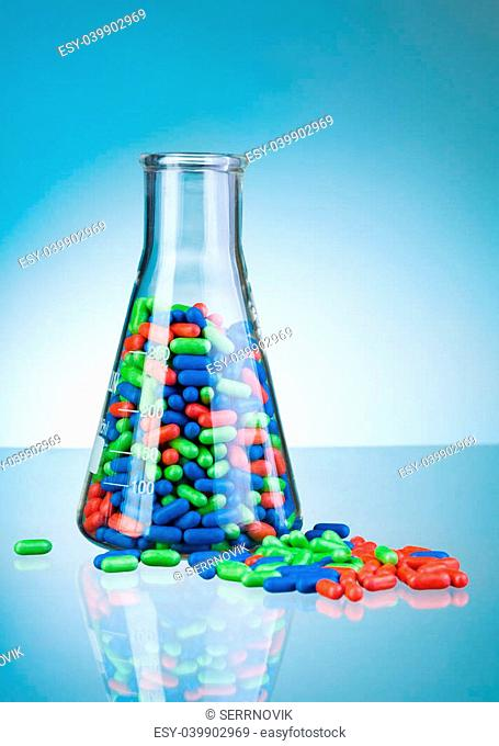 Different green blue and red tablet pills drugs on blue label table and in lab flask glass container