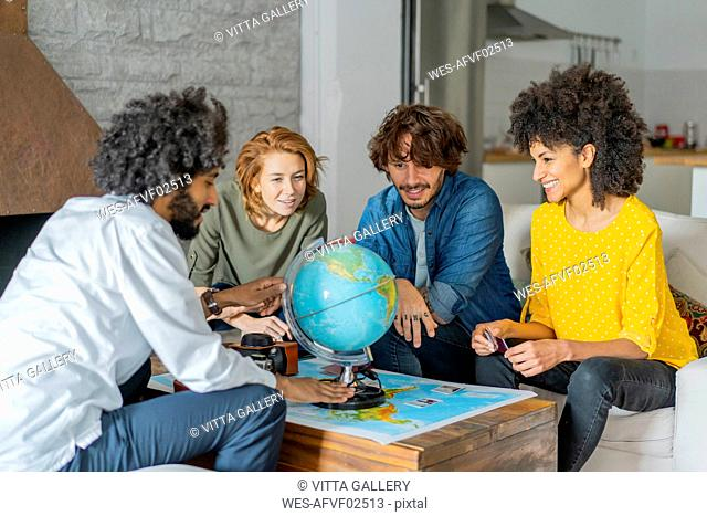Friends meeting to plan vacations, checking map and globe