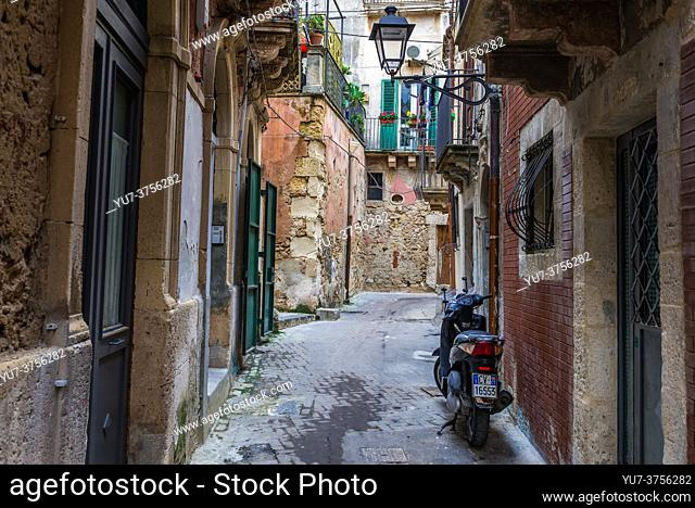 Narrow street on the Ortygia island, historical part of Syracuse city, southeast corner of the island of Sicily, Italy