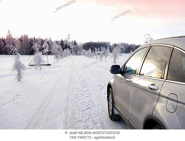 Parked car on snowy rural road in Estonia. White frost, snow covered trees by alley. Evening light reflecting on car glass