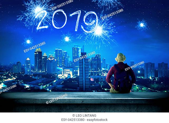 Rear view of asian traveler man sitting on the rooftop looking at 2019 from sparkling fireworks on the city at night. Happy New Year 2019