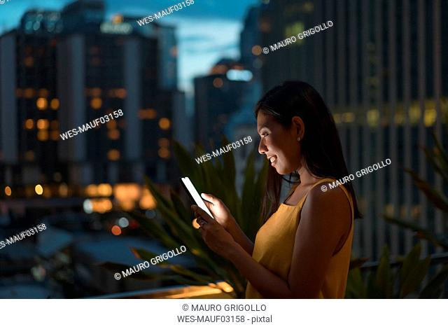 Smiling woman standing on roof terrace at dusk looking at cell phone, Bangkok, Thailand