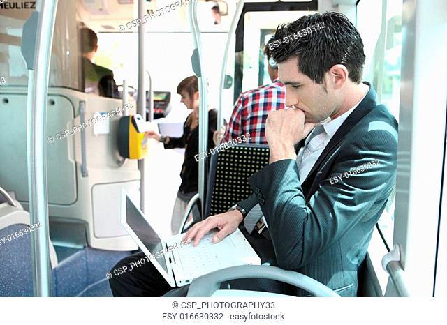 Man using laptop computer on a tram