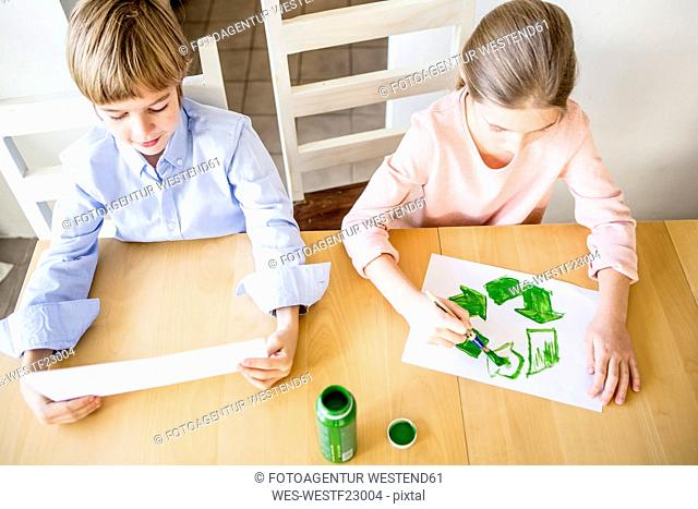 Brother and sister painting recycling symbols