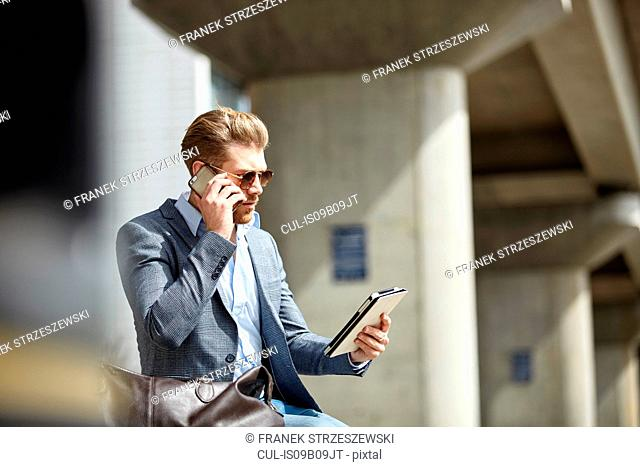 Young businessman talking on smartphone and using digital tablet in city, London, UK