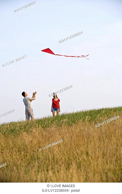 A young couple flying a red kite