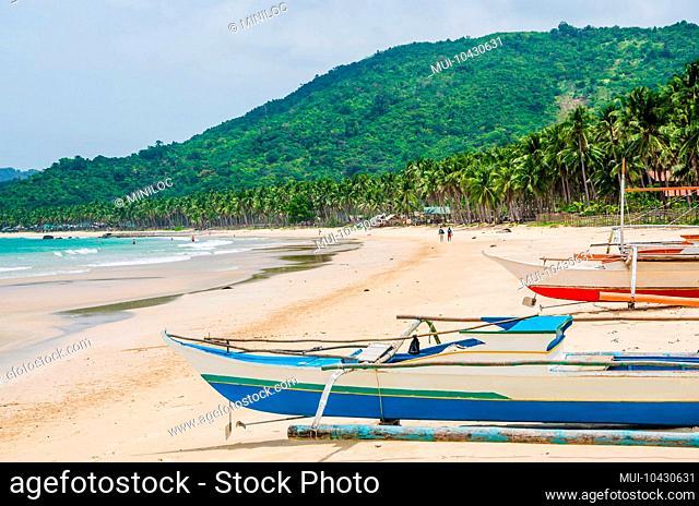 Local boats on Nacpan Beach on sunny day. El Nido, Palawan, Philippines