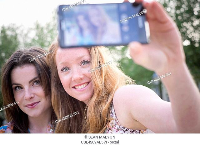 Close up of two young female friends in park taking selfie on smartphone
