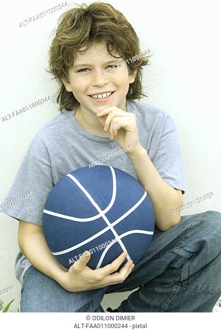 Boy holding basketball, portrait