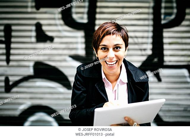 Portrait of happy woman with tablet