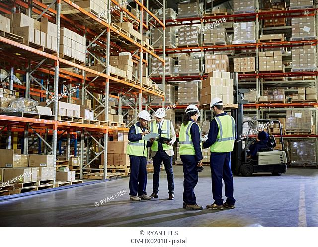 Workers meeting and talking in distribution warehouse