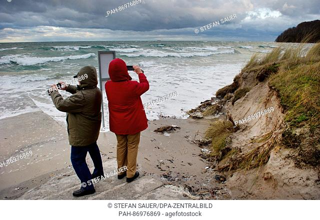 Tourists photograph waves generated by storm 'Axel' from the beach in the Ruegen island town of Binz, Germany, 04 January 2017