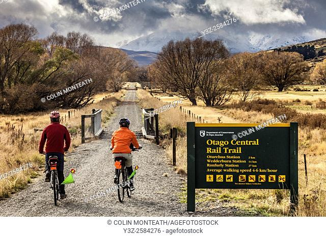 Cyclists on Otago Rail Trail near Oturehua, gathering snow storm, Central Otago, New Zealand