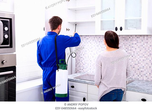 Woman Showing At Pest Control Worker Spraying Insecticide On Shelf Of Domestic Kitchen