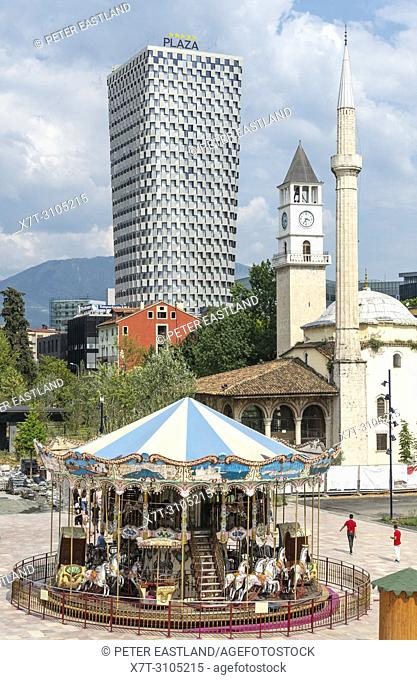 A childrens carousel in Skanderbeg Square with the Et'hem Bey Mosque, the clock tower and the Plaza Hotel in the background, Tirana, Albania,