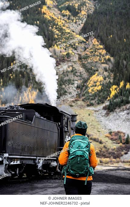 Tourist walking in mountain and looking at steam locomotive