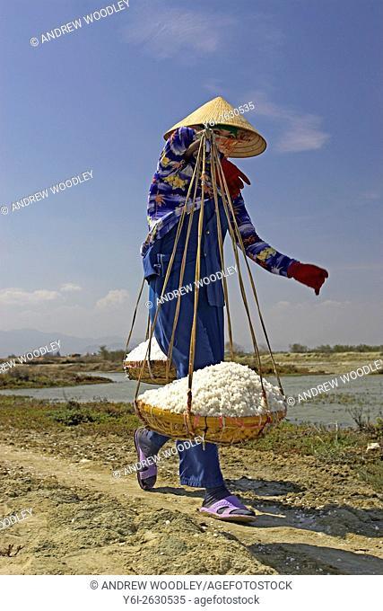 Woman in conical hat carries salt in wicker pannier baskets Phan Thiet Vietnam