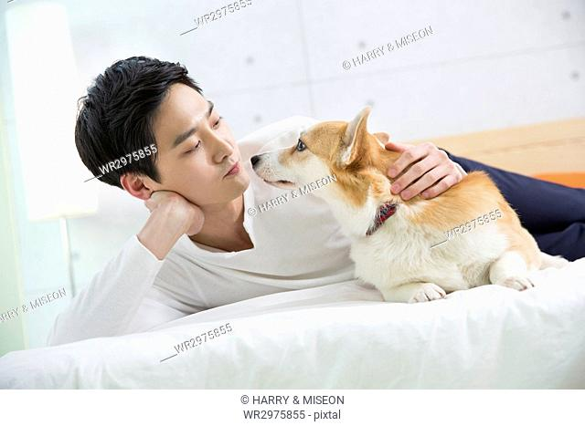 Young bachelor playing with his pet dog