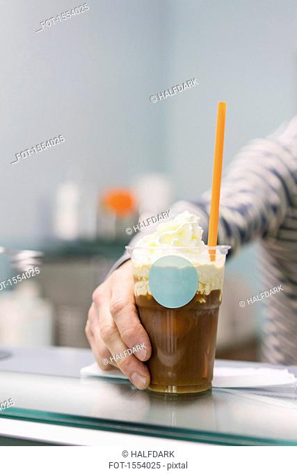 Detail of hand holding iced coffee on counter