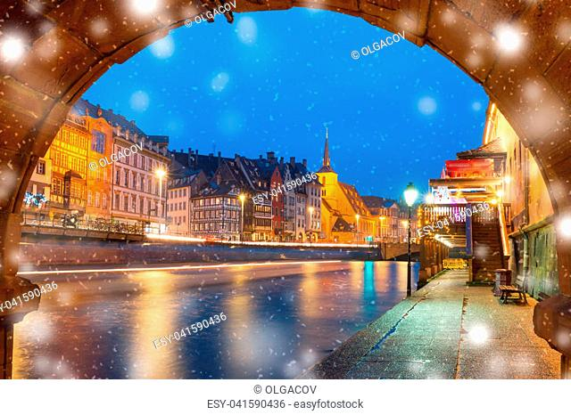Picturesque Christmas quay and church of Saint Nicolas with mirror reflections in the river Ile at snowy christmas night, Strasbourg, Alsace, France