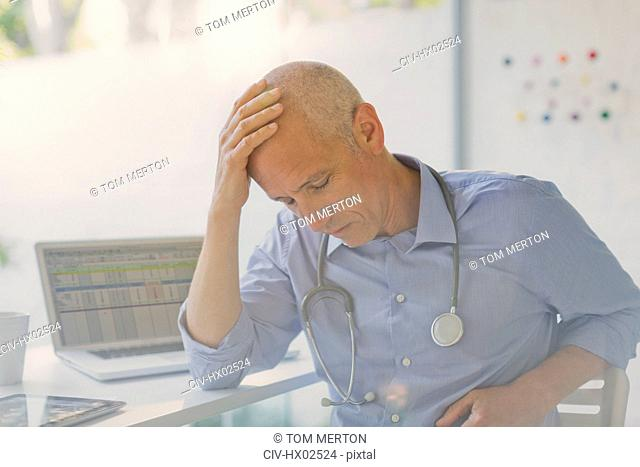 Tired, stressed male doctor with head in hands in doctor's office