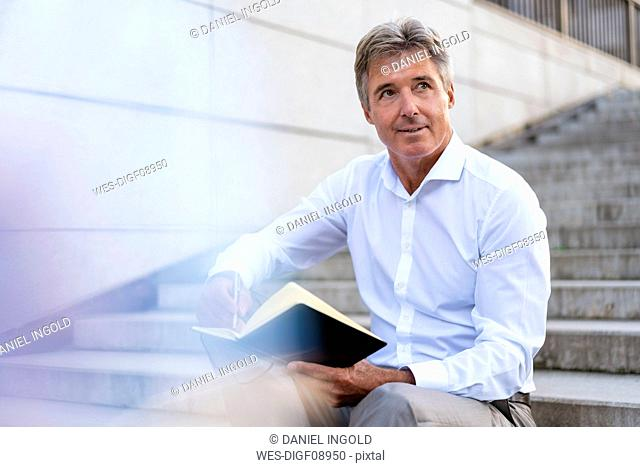 Mature businessman sitting on stairs with notebook
