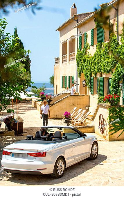Porter welcoming couple driving convertible to boutique hotel, Majorca, Spain