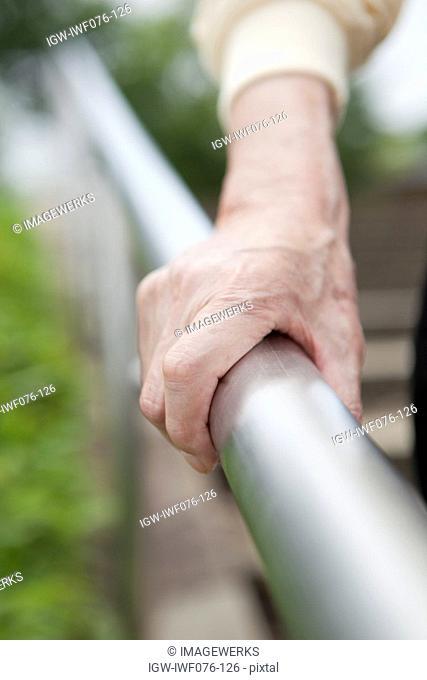 Japan, Tokyo Prefecture, Senior man's hand holding railings, close-up