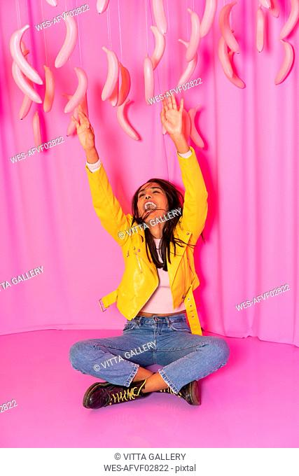 Young woman screaming at an indoor theme park with dangling pink bananas