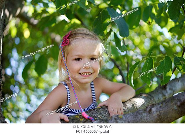 Portrait of cheerful girl climbing tree in yard