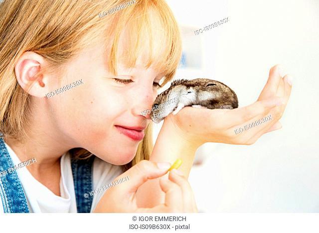 Girl feeding hamster