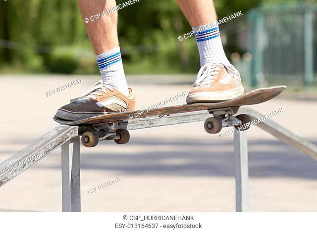 Skater doing noseslide on fun-box in skatepark