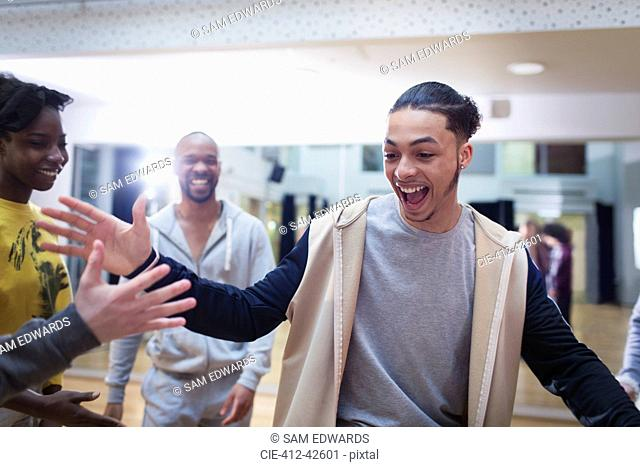 Enthusiastic teenage boy high-fiving classmate in dance class studio