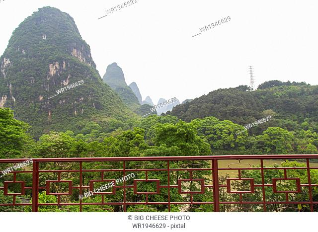 View of mountains beyond a fenced patio, Yangshuo, China