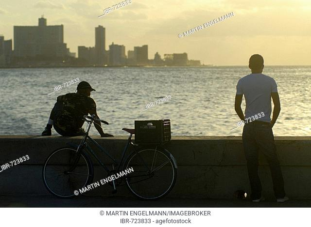 Two men and a bicycle at the Malecón, sunset, Havana, Cuba