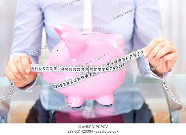 Businessperson With Piggybank And Measuring Tape