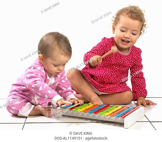 Baby girl (8 months) and young girl (2 years) playing with colourful toy xylophone