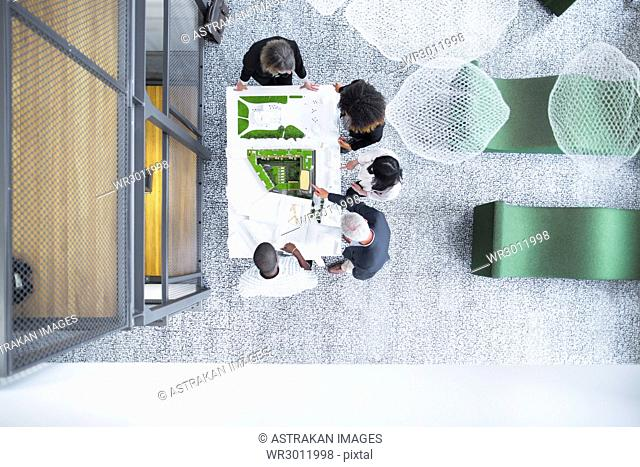 Overhead view of architects discussing blueprint