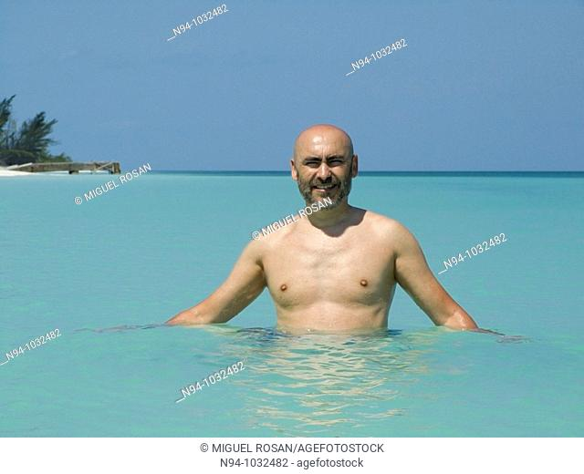 Young man, bald with a beard, bathing in the edge of the Caribbean beach in Cayo Levisa Cuba