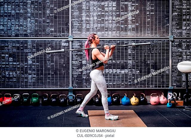 Young woman lifting weight bar in gym