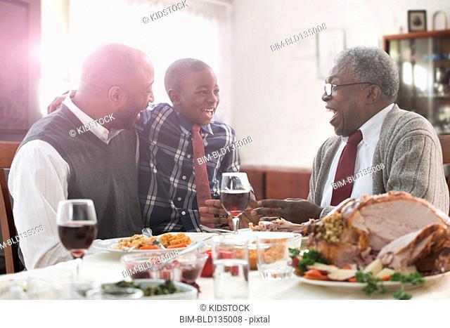 Three generations of men talking at holiday table