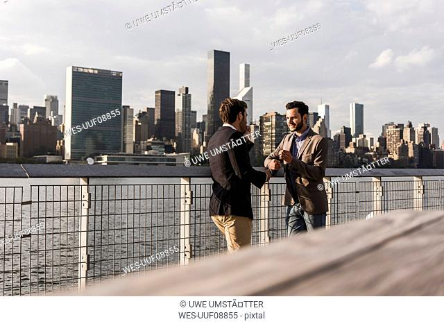 USA, New York City, two businessmen talking at East River