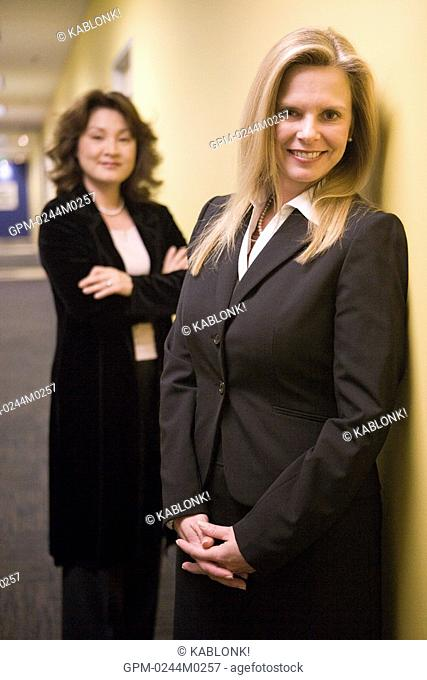 Portrait of two multi-ethnic businesswomen standing in office corridor, looking at camera
