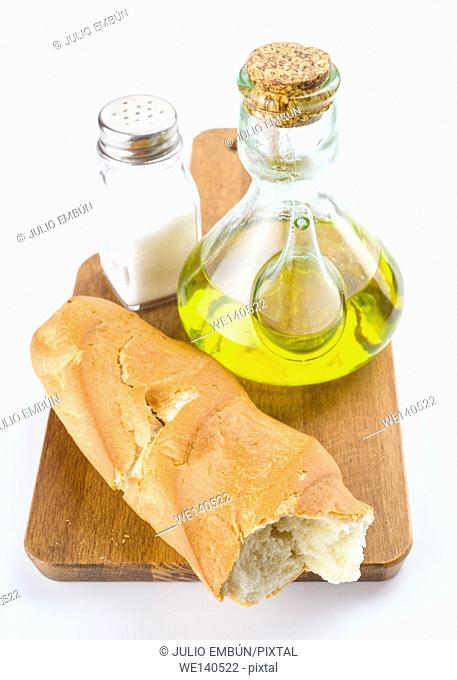 Spanish bread with oil and salt on wooden board isolated on white
