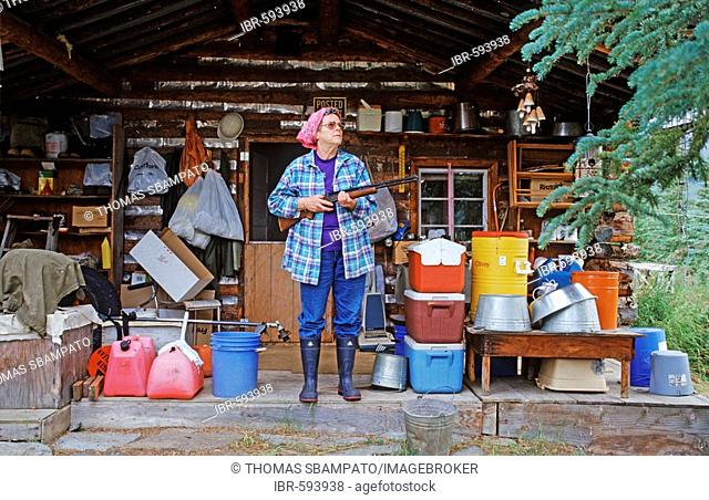 Armed woman standing in front of her log home, Brooks Range, Alaska, USA