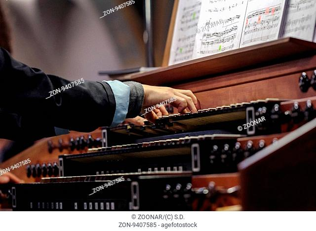 Close up view of a organist playing a pipe organ with motion blur