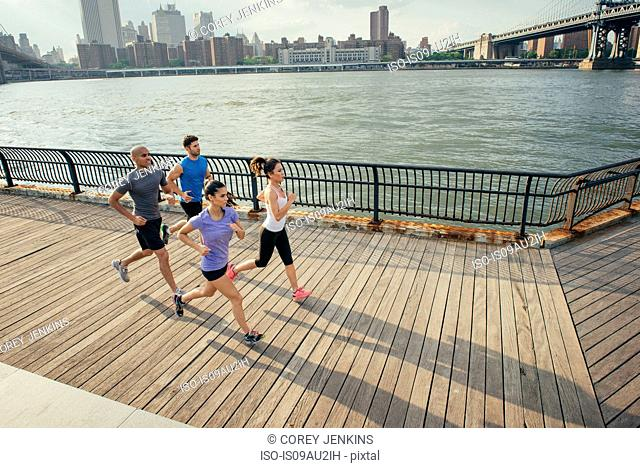 Four adult runners running along riverside, Brooklyn, New York, USA