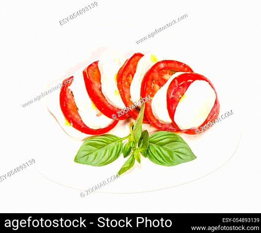 italian cuisine insalata caprese (caprese salad) - top view of sliced mozzarella cheese and tomato with basil twig on plate isolated on white background