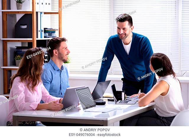 Group Of Businesspeople Working On Laptop During Meeting In Office